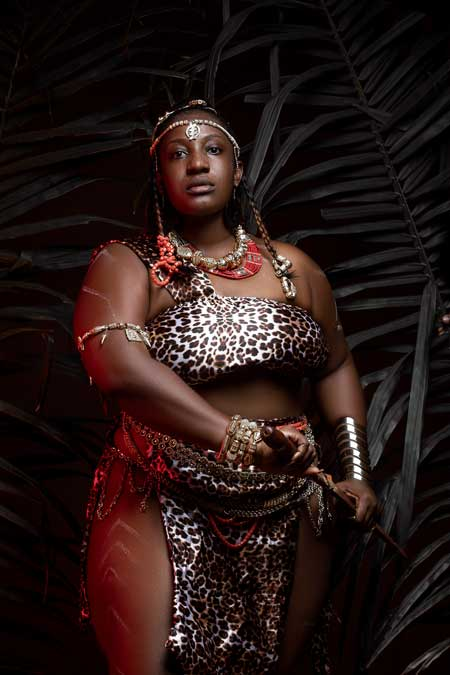 Dreamy-chubby-African-woman-in-traditional-wear-in-darkness