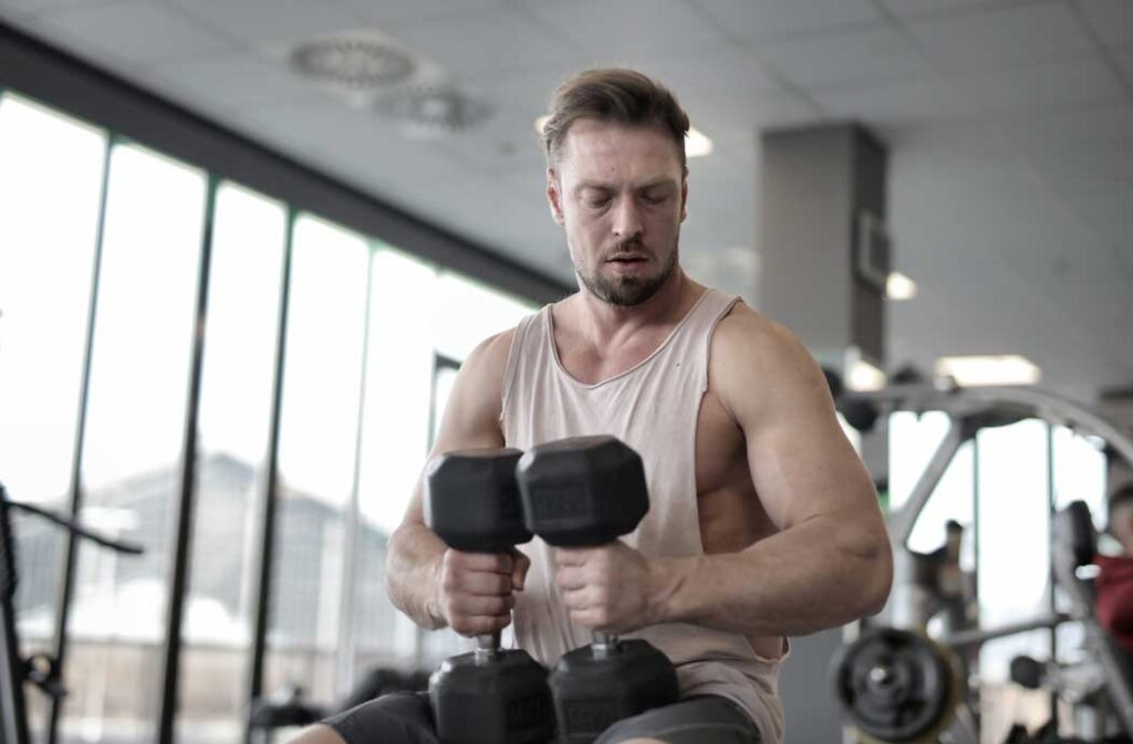 Man-In-Tank-Top-Holding-Dumbbells
