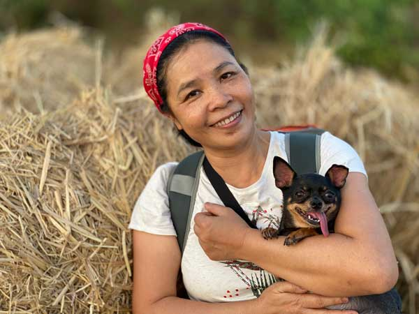Ethnic-woman-hugging-small-dog-in-field